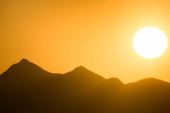 Solnedgång över berg under orange himmel Arkivfoton