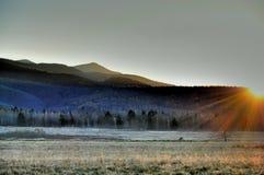 Solnedgång över bergen Arkivfoto