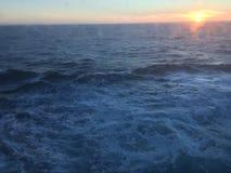 Solnedgång över bergen som bryter till och med den tunga molnräkningen på Stilla havet i Alaska Amerikas förenta stater royaltyfri foto