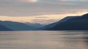 Solnedgång över bergen som bryter till och med den tunga molnräkningen på Stilla havet i Alaska Amerikas förenta stater arkivbild