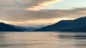 Solnedgång över bergen som bryter till och med den tunga molnräkningen på Stilla havet i Alaska Amerikas förenta stater arkivfoto