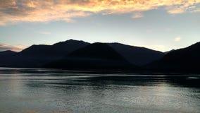 Solnedgång över bergen som bryter till och med den tunga molnräkningen på Stilla havet i Alaska Amerikas förenta stater arkivfoton