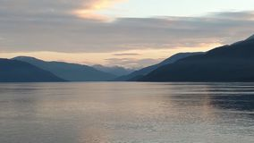 Solnedgång över bergen som bryter till och med den tunga molnräkningen på Stilla havet i Alaska Amerikas förenta stater royaltyfria foton