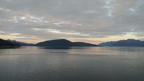 Solnedgång över bergen som bryter till och med den tunga molnräkningen på Stilla havet i Alaska Amerikas förenta stater arkivbilder