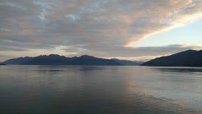 Solnedgång över bergen som bryter till och med den tunga molnräkningen på Stilla havet i Alaska Amerikas förenta stater royaltyfri bild