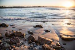 Solnedgång över bränning på kust Arkivfoto