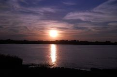 Solnedgång över breda flodmynningen Arkivbilder