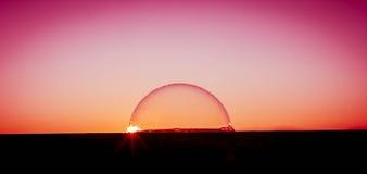 Solnedgång över bubblavärlden Royaltyfri Bild