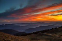 Solnedgång över dalar Arkivfoto