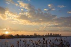 Solnedgång över den djupfrysta Tisa floden som täckas med snö Arkivfoton