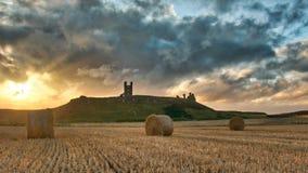 Solnedgång över den Dunstanburgh slotten Royaltyfri Bild