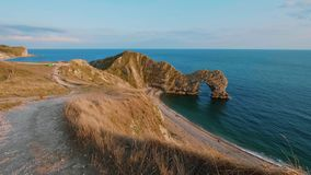 Solnedgång över den Durdle dörren - den mest berömda gränsmärket i Devon England stock video