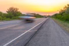 Solnedgång över den lantliga vägen med fartfyllda bilar Arkivbild
