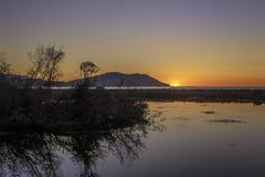 Solnedgång över den sötvattens- fjärden royaltyfria foton