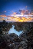Solnedgång över den steniga kustlinjen Royaltyfri Bild