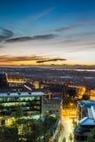 Solnedgång över den tända staden Arkivfoto