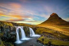 Solnedgång över det Kirkjufellsfoss vattenfall- och Kirkjufell berget i Island arkivfoton