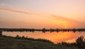 Solnedgång över det livliga landskapet för sjö arkivbild