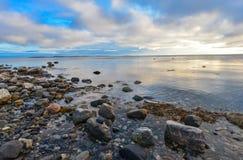Solnedgång över det vita havet, stenar, reflexion Arkivbild