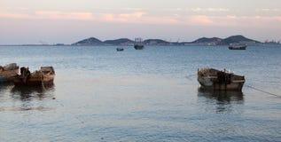 Solnedgång över en hamn Arkivbilder