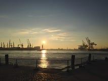 Solnedgång över en hamn och skeppsdockor Arkivfoton
