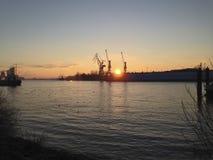 Solnedgång över en hamn och skeppsdockor Royaltyfri Foto