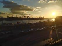 Solnedgång över en hamn och skeppsdockor Arkivfoto