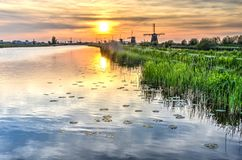 Solnedgång över en kanal i Kinderdijk royaltyfri bild