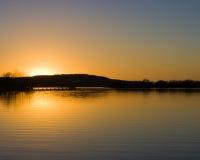 Solnedgång över en sjö Royaltyfri Fotografi
