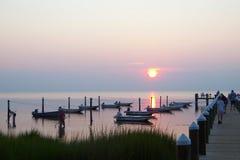 Solnedgång över en skeppsdocka för Chesapeakefjärd med fartyg Royaltyfri Foto