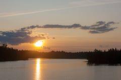 Solnedgång över en skogsjö Royaltyfri Fotografi