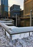 Solnedgång över en snöig Chicagoland och Chicago River i vinter arkivfoto