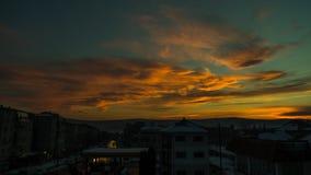 Solnedgång över en stad med orange och blå färg royaltyfri fotografi