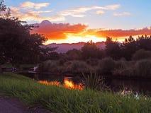 Solnedgång över en stillsam ström Arkivbild