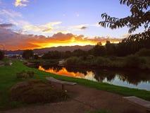 Solnedgång över en stillsam ström Arkivfoton