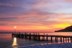 Solnedgång över en strand och en träpir Arkivbilder