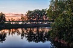 Solnedgång över en tyst sjö Arkivbild