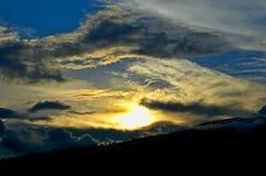 Solnedgång över ett berg Arkivfoto