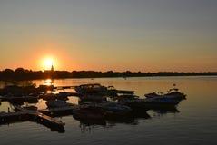 Solnedgång över ett damm med churh i tillbaka royaltyfria foton