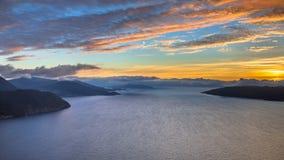 Solnedgång över fjorden runt om Vestnes i Norge arkivbilder