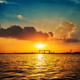 Solnedgång över floden och industriell skeppsbyggeri på bakgrund Arkivfoto