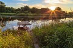 Solnedgång över floden, träbro Arkivfoto