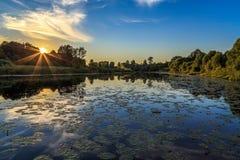 Solnedgång över floden, varm dag för afton Arkivfoto