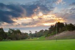 Solnedgång över golfbana Royaltyfri Bild