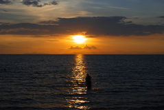 Solnedgång över havet med människan Arkivfoto