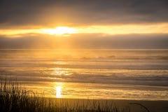 Solnedgång över havet med moln Arkivbild