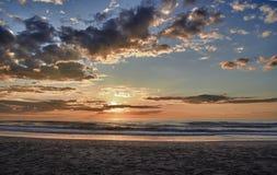 Solnedgång över havet med moln Arkivfoton