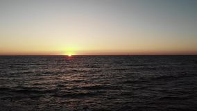 Solnedgång över havet med vågor som slår stranden och den lilla yachten på horisont Solnedgång med solvägen på det krabba havshav lager videofilmer