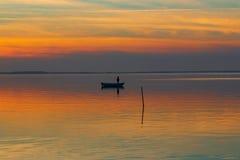 Solnedgång över havet och ett litet fartyg arkivfoto