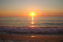 Solnedgång över havet och vågen Arkivbilder